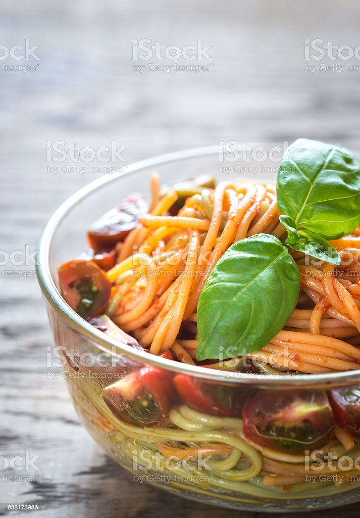 Bowl of colorful spaghetti with cherry tomatoes stock photo