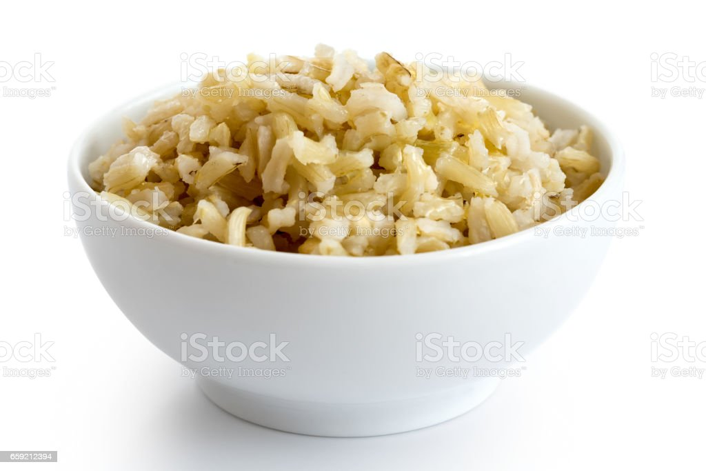 Bowl of cooked long grain brown rice isolated on white. stock photo