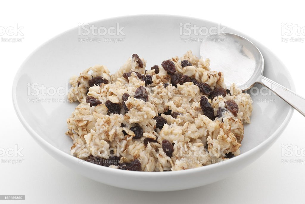 bowl of cooked oatmeal with raisins royalty-free stock photo