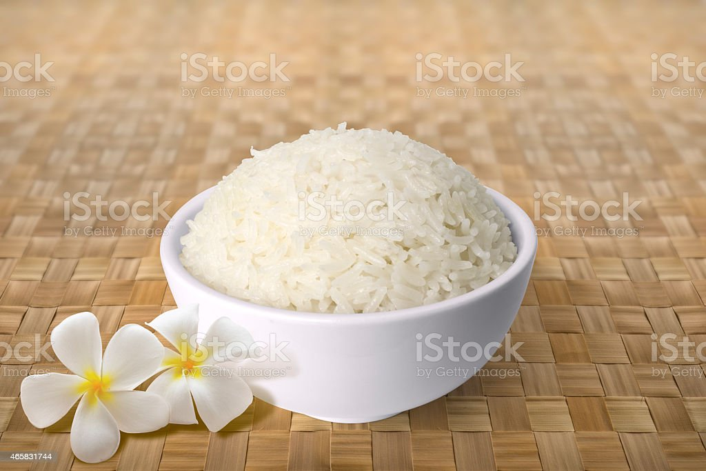 Bowl of Cooked Rice on straw mat with Frangipani stock photo