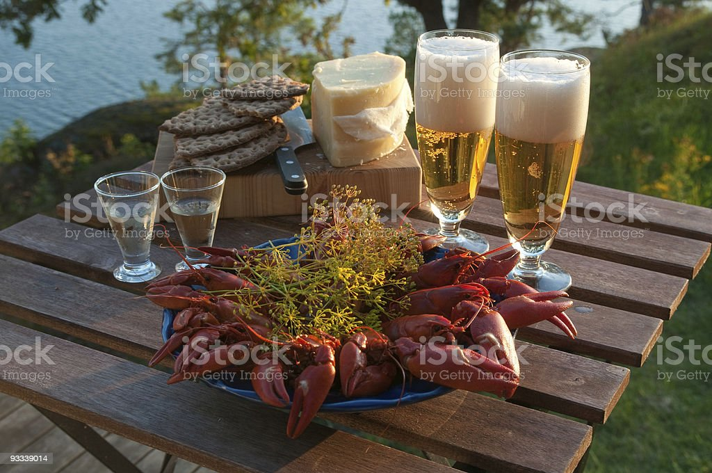 Bowl of crayfish on a picnic table outdoors with beer stock photo