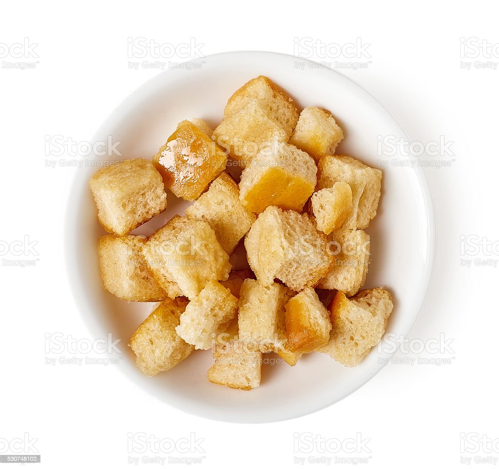 Bowl of croutons isolated on white, top view stock photo