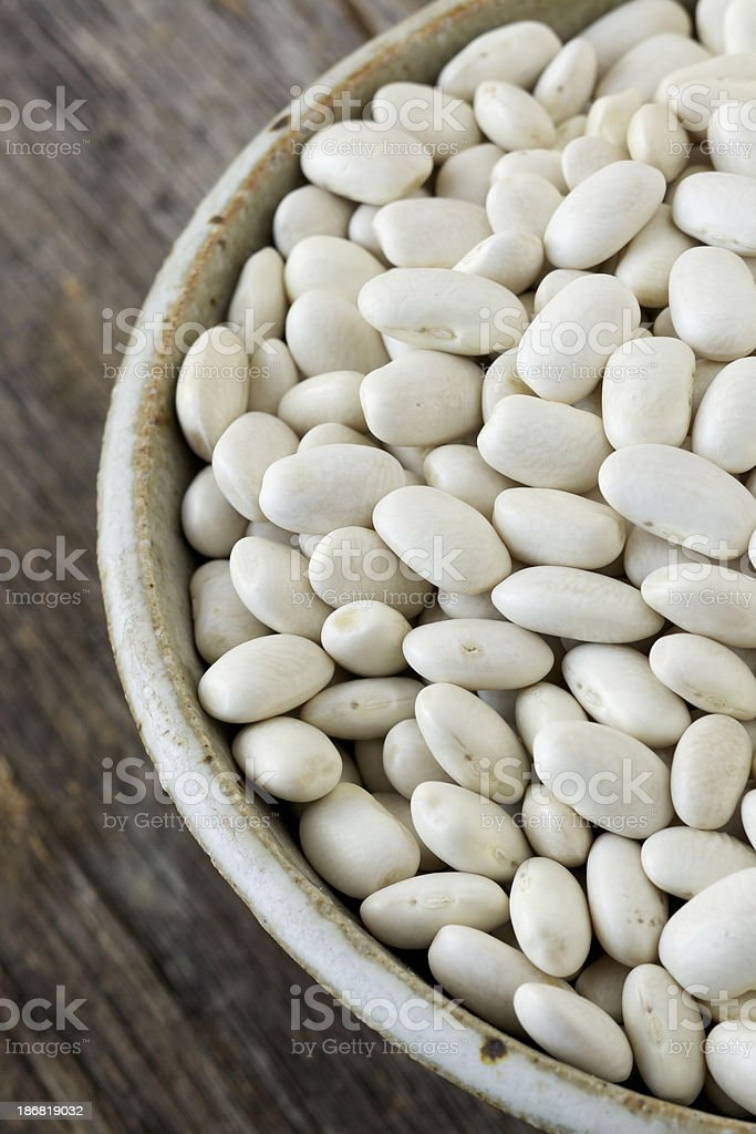 Bowl of dried cannellini beans on rustic wood surface royalty-free stock photo