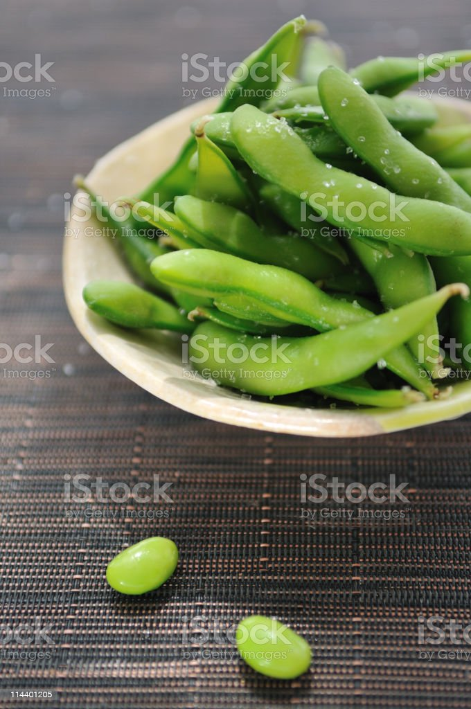 Bowl of edamame beans on bamboo mat stock photo