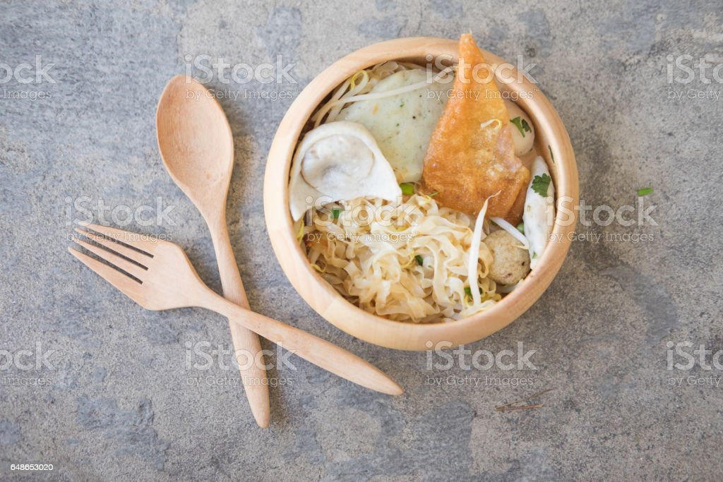 Bowl of egg noodles with dumpling and vegetable in wooden bowl stock photo
