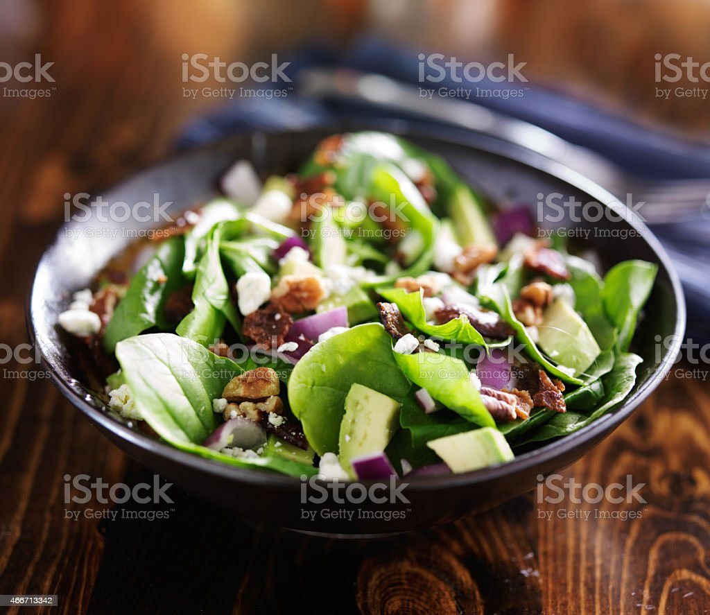 bowl of fresh avocado spinach salad stock photo