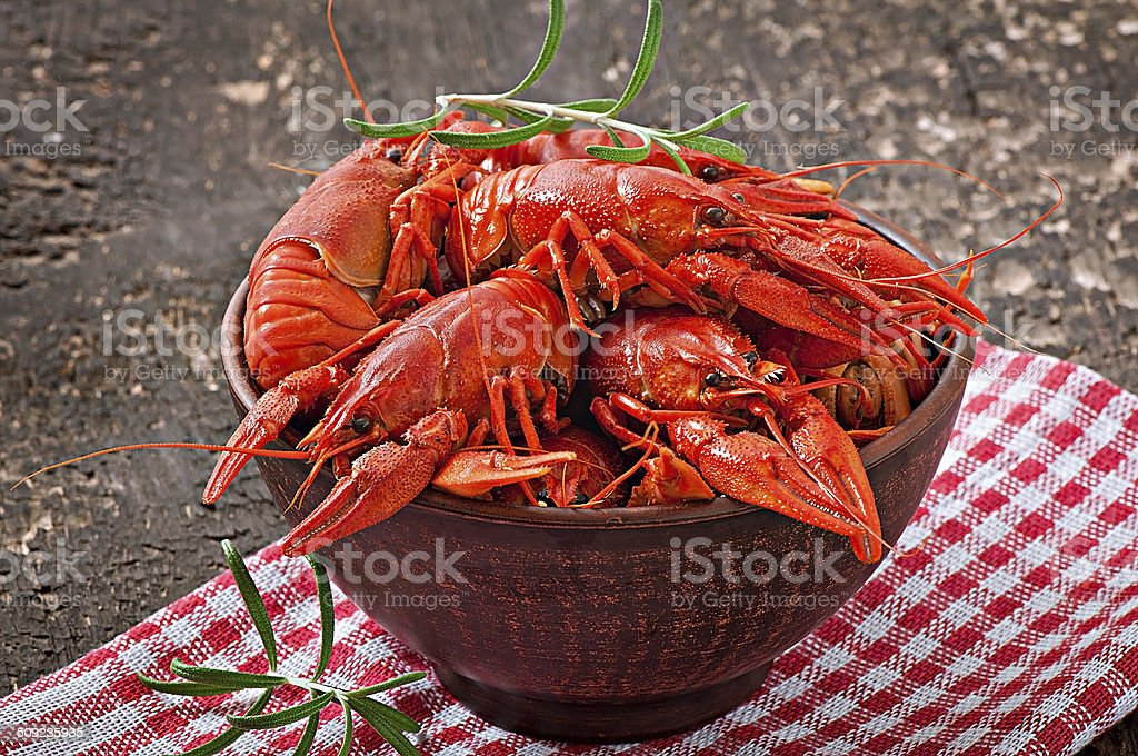 Bowl of fresh boiled crawfish on the old wooden background stock photo