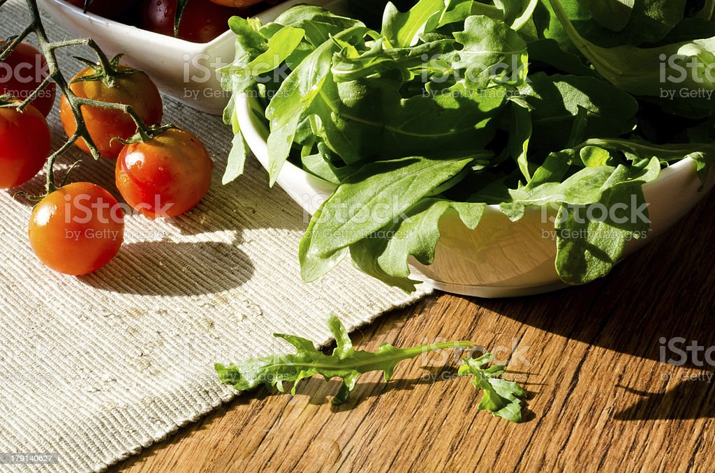 bowl of fresh green, natural arugula and cherry tomatoes royalty-free stock photo