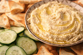 A bowl of fresh hummus and cucumbers