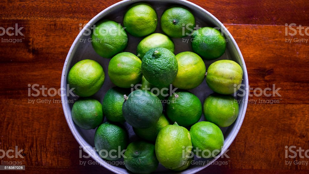 Bowl of Fresh Limes On Table stock photo