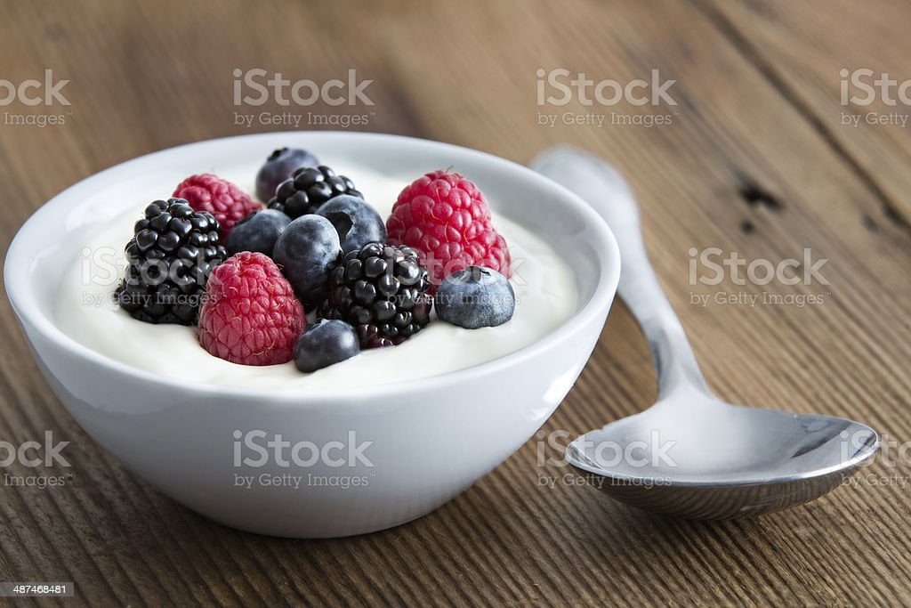 Bowl of fresh mixed berries and yogurt stock photo