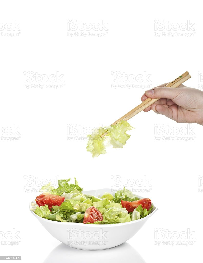 Bowl of fresh salad isolated with chinese chopticks stock photo