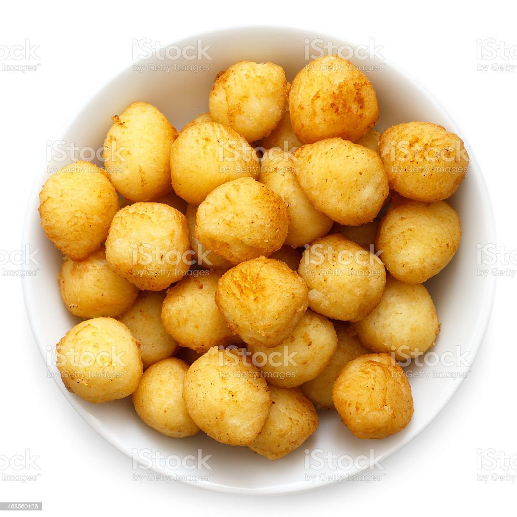 Bowl of fried small potato balls on white. stock photo