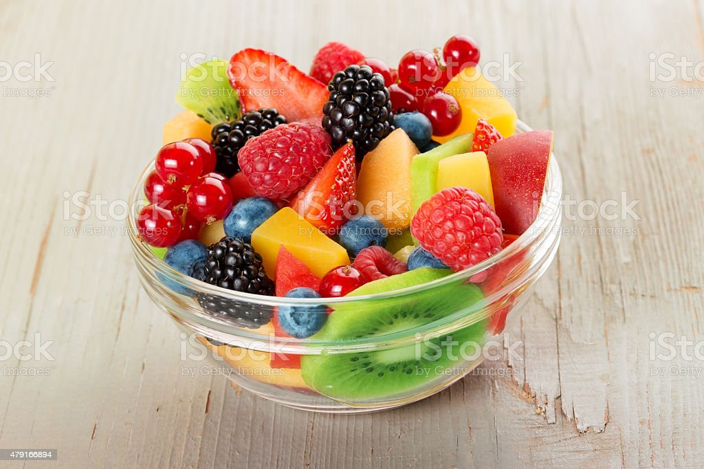 bowl of fruit salad isolated on wood table stock photo