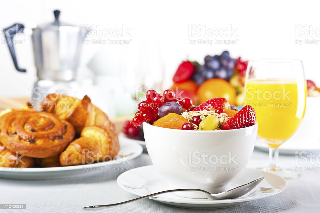 Bowl of fruit with glass of orange juice and croissants stock photo