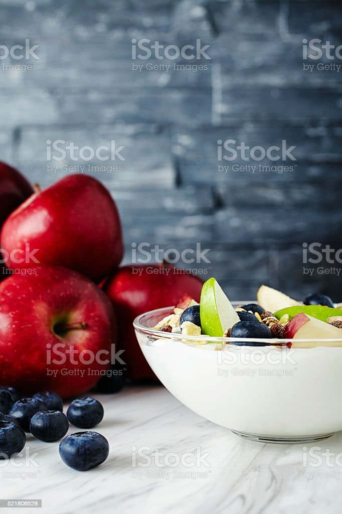 Bowl of granola with apple slices stock photo