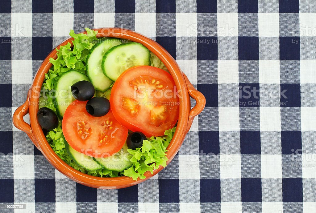 Bowl of Greek salad on checkered cloth with copy space stock photo