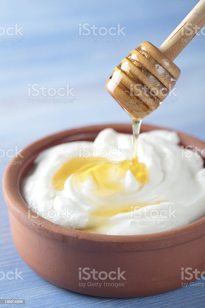 Bowl of Greek yogurt being topped with honey stock photo
