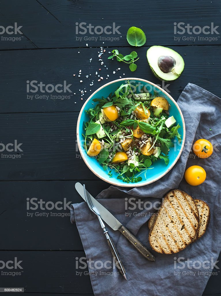 Bowl of green salad with avocado, arugula, cherry tomatoes and stock photo
