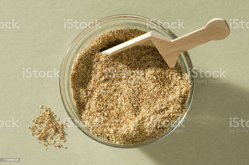 Bowl of ground Flax w/wooden scoop-isolated close-up royalty-free stock photo