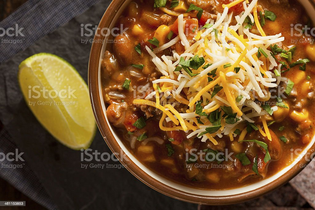 Bowl of homemade chili topped with cheese and slice of lemon stock photo
