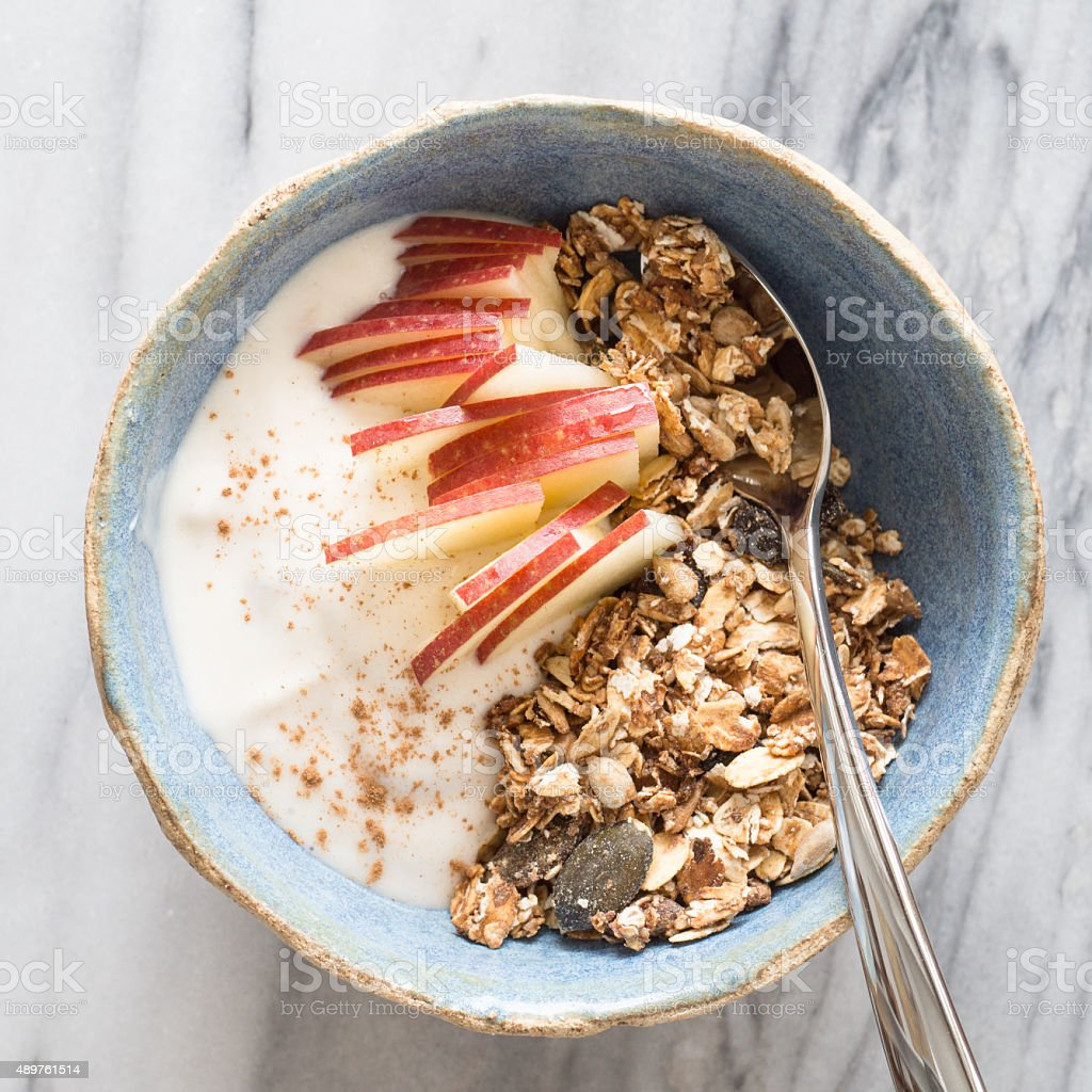 Bowl of homemade granola with apple slices and yogurt stock photo
