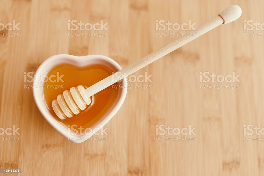 Bowl of honey on wooden table. stock photo