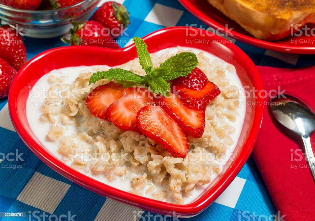 bowl of hot oatmeal served with fresh strawberries and toast stock photo