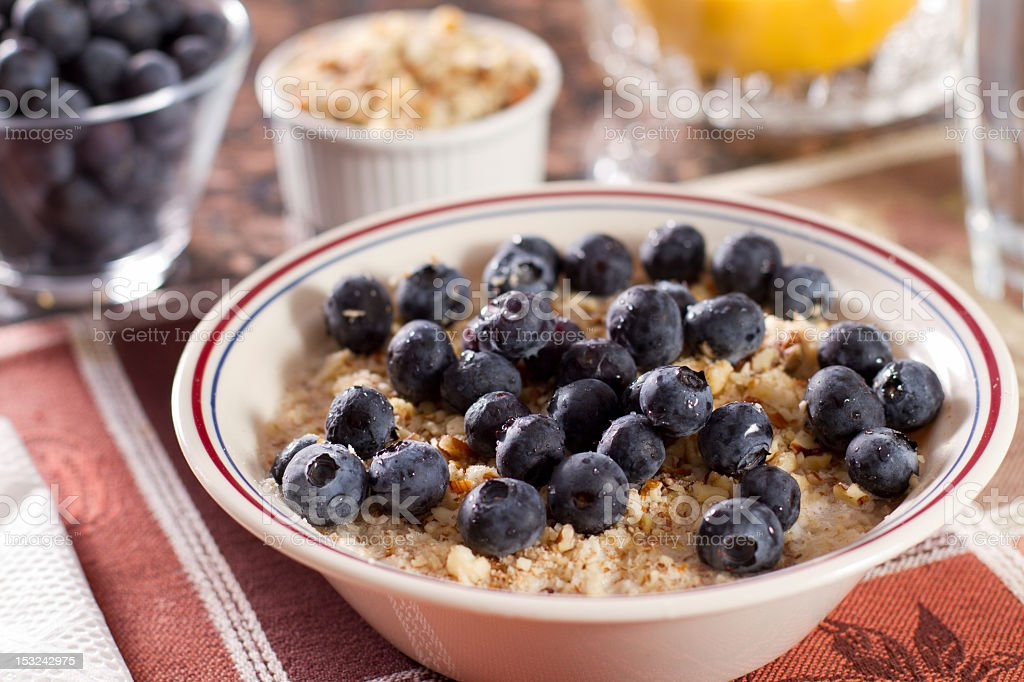 Bowl of hot oatmeal with ground nuts and blueberries. stock photo