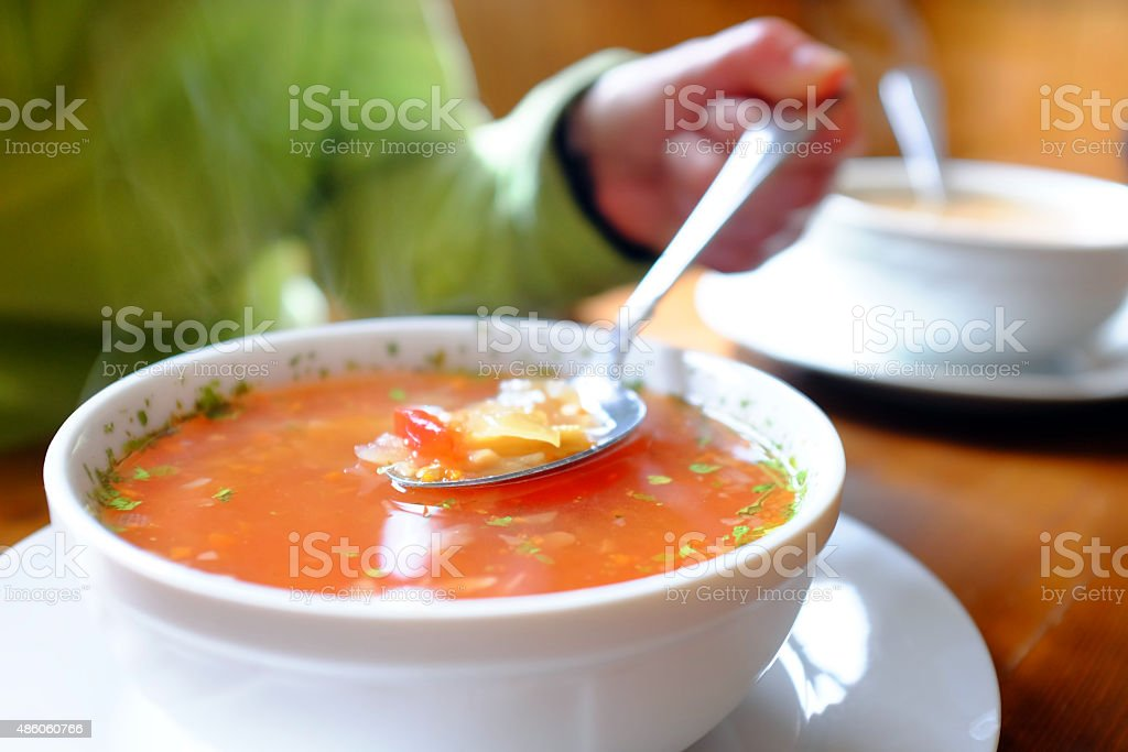 Bowl of hot vegetable soup and hand holding spoon. stock photo