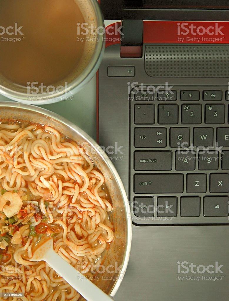 Bowl of instant noodles and coffee next to a laptop foto de stock libre de derechos