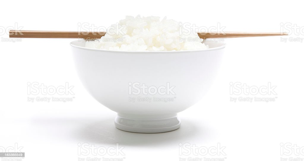 Bowl of Japanese rice with bamboo chopsticks resting on top royalty-free stock photo