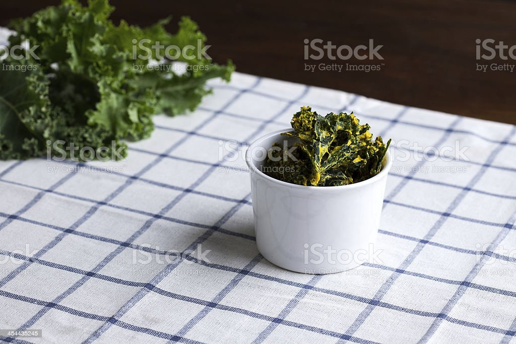 bowl of kale chips on kitchen towel royalty-free stock photo