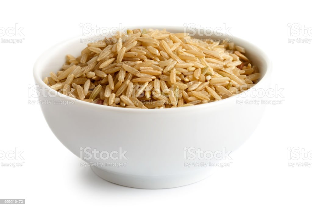 Bowl of long grain brown rice isolated on white. stock photo