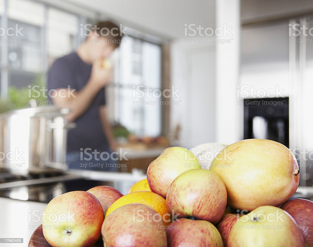 Bowl of mangos and nectarines with man in background eating royalty-free stock photo