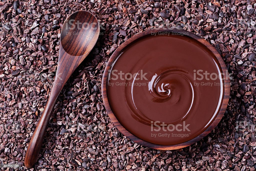 Bowl of melted chocolate on crushed cocoa beans, nibs background stock photo