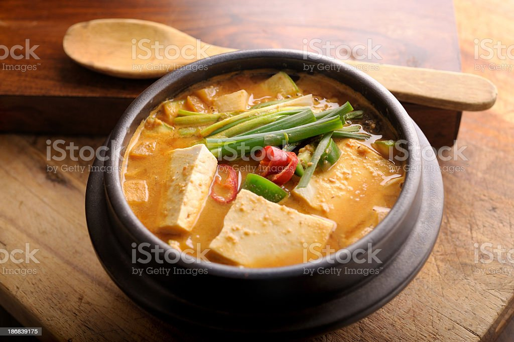 A bowl of miso soup with a wooden spoon stock photo