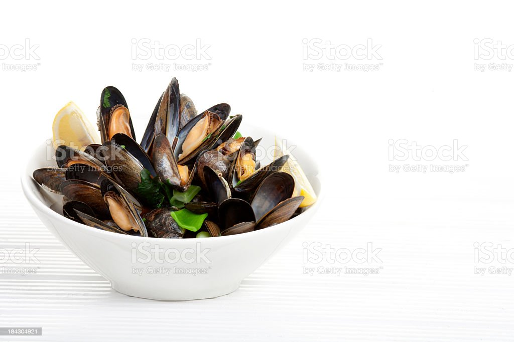 A bowl of mussels garnished with lemons on a white table  stock photo