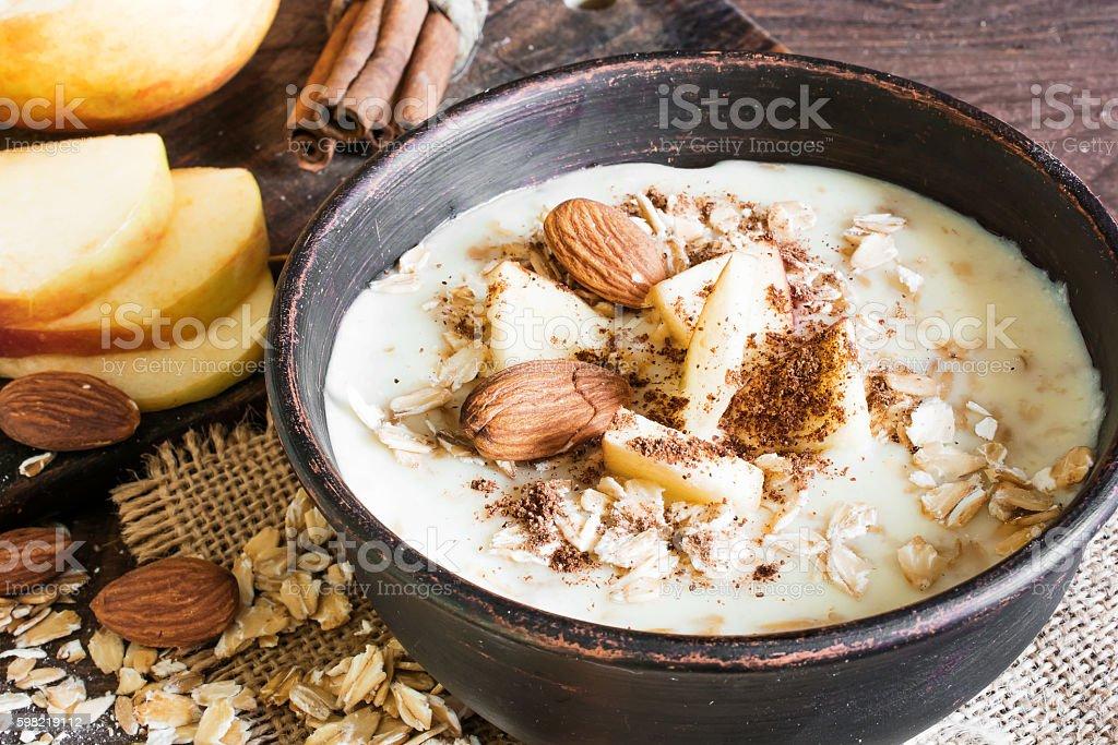 bowl of oatmeal porridge with apple, cinnamon and almonds stock photo