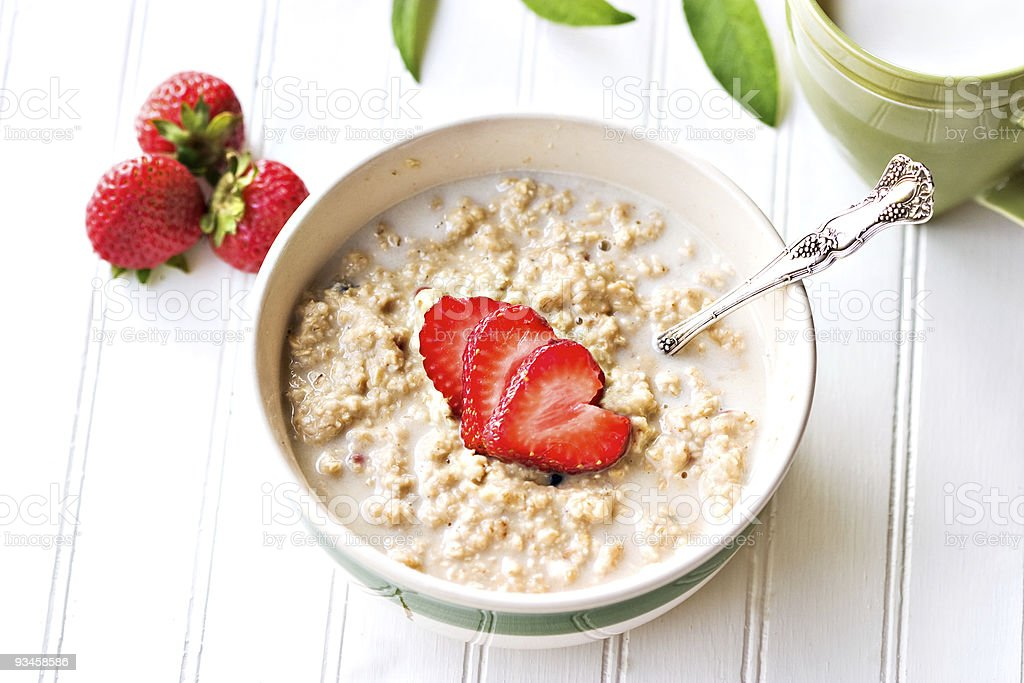 A bowl of oatmeal with strawberries stock photo