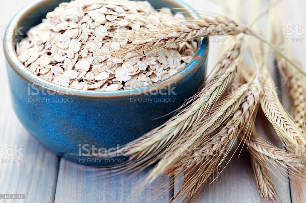 A bowl of oats with wheat next to it stock photo