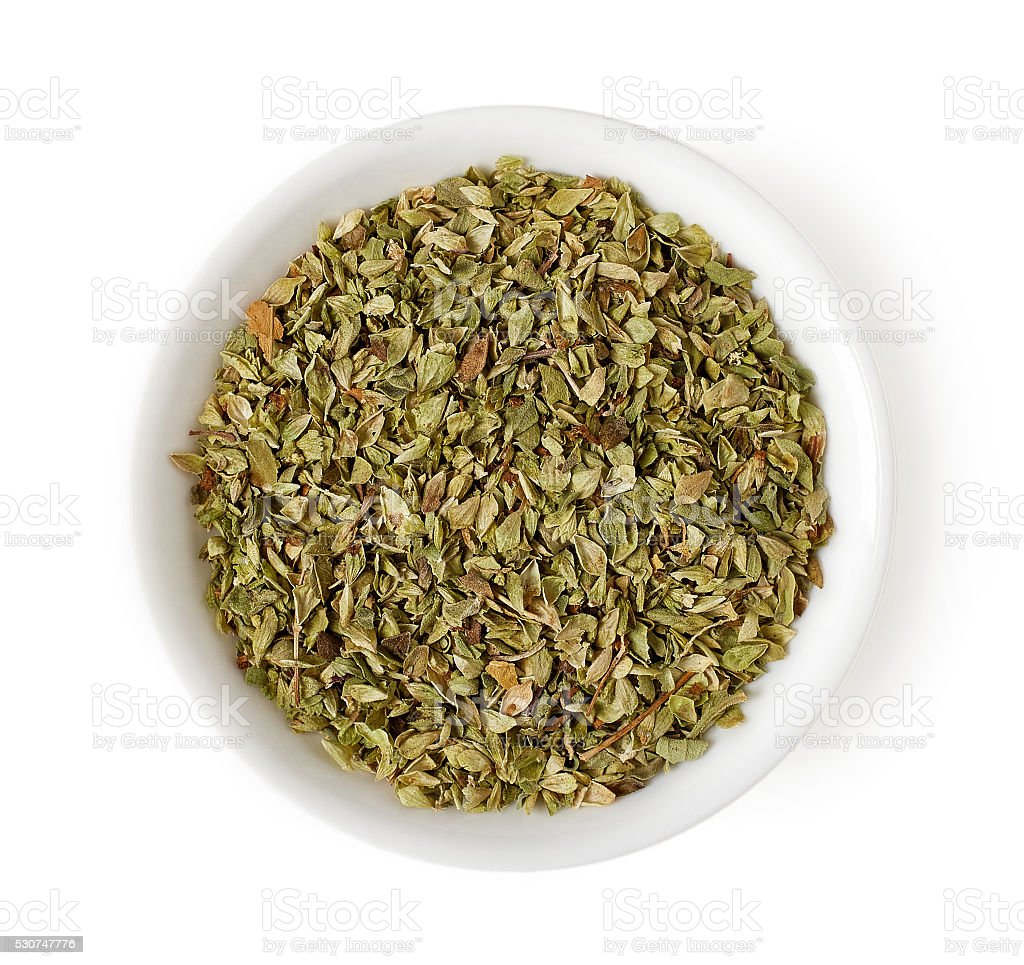 Bowl of oregano leaves isolated on white, top view stock photo