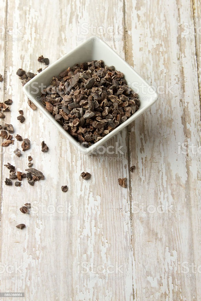 Bowl of Organic Cacao Nibs on a wood plank board stock photo