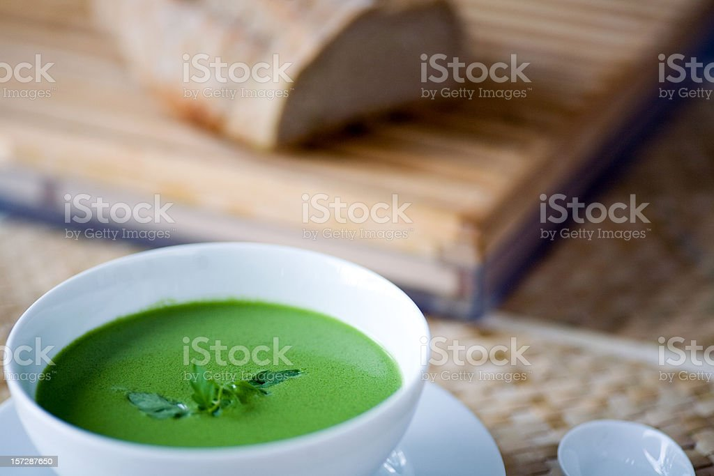 bowl of pea green herbal soup stock photo