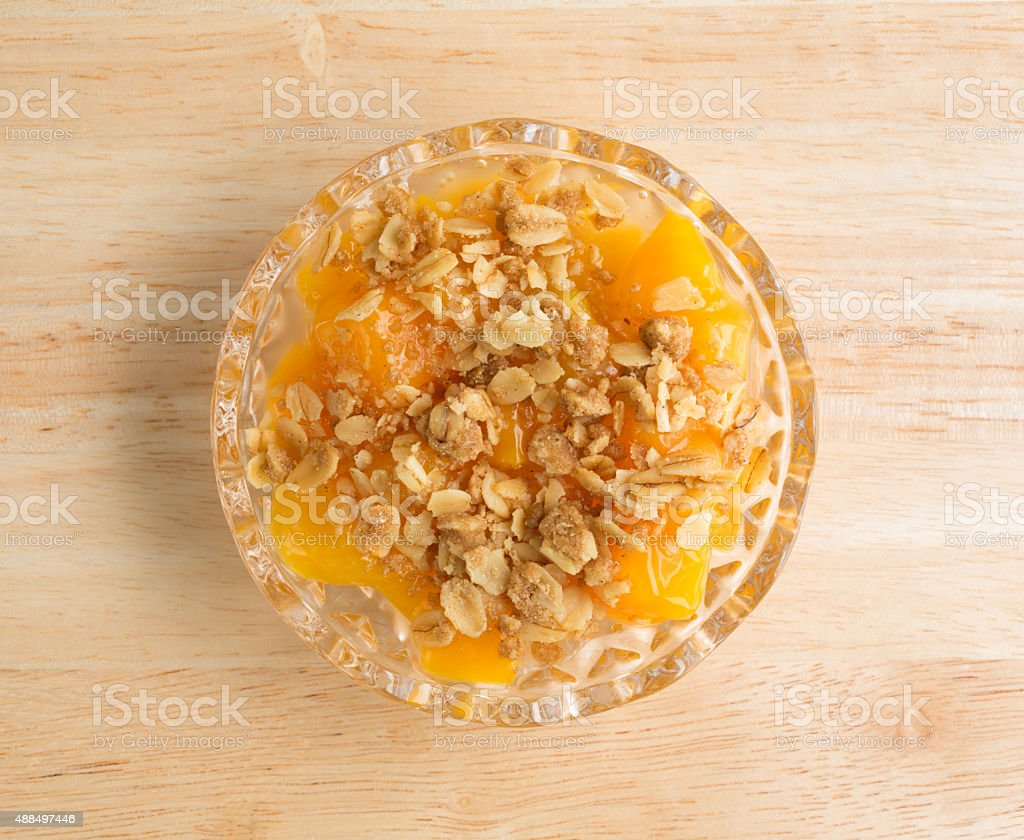 Bowl of peaches brown sugar and oats on counter top stock photo