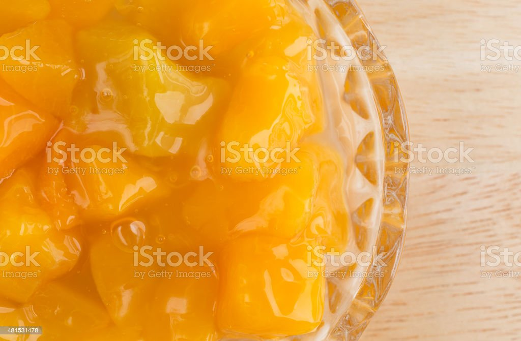 Bowl of peaches in heavy syrup on wood table stock photo