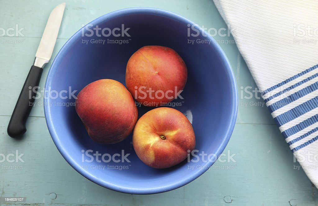 Bowl of Peaches on Blue Table stock photo