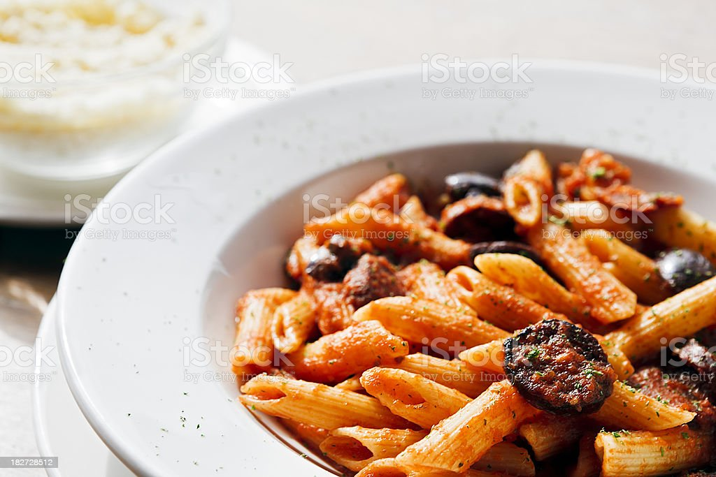 Bowl of penne pasta with chourizo and tomato sauce stock photo