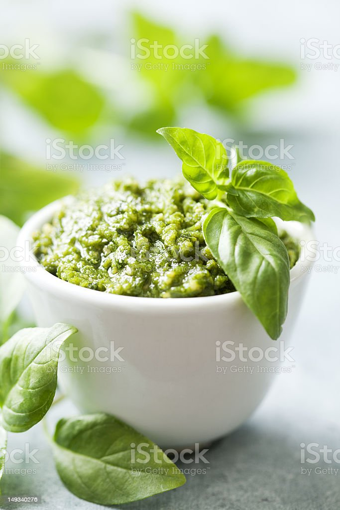 Bowl of pesto with plant leaves stock photo