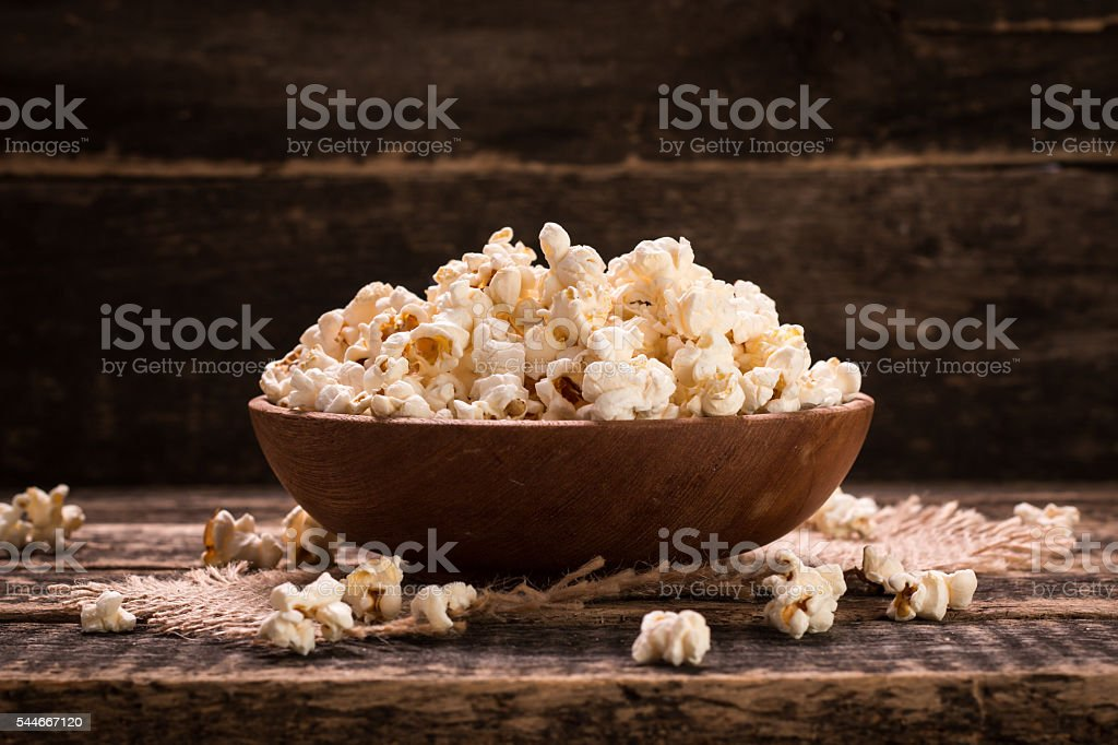 bowl of popcorn on a wooden table stock photo